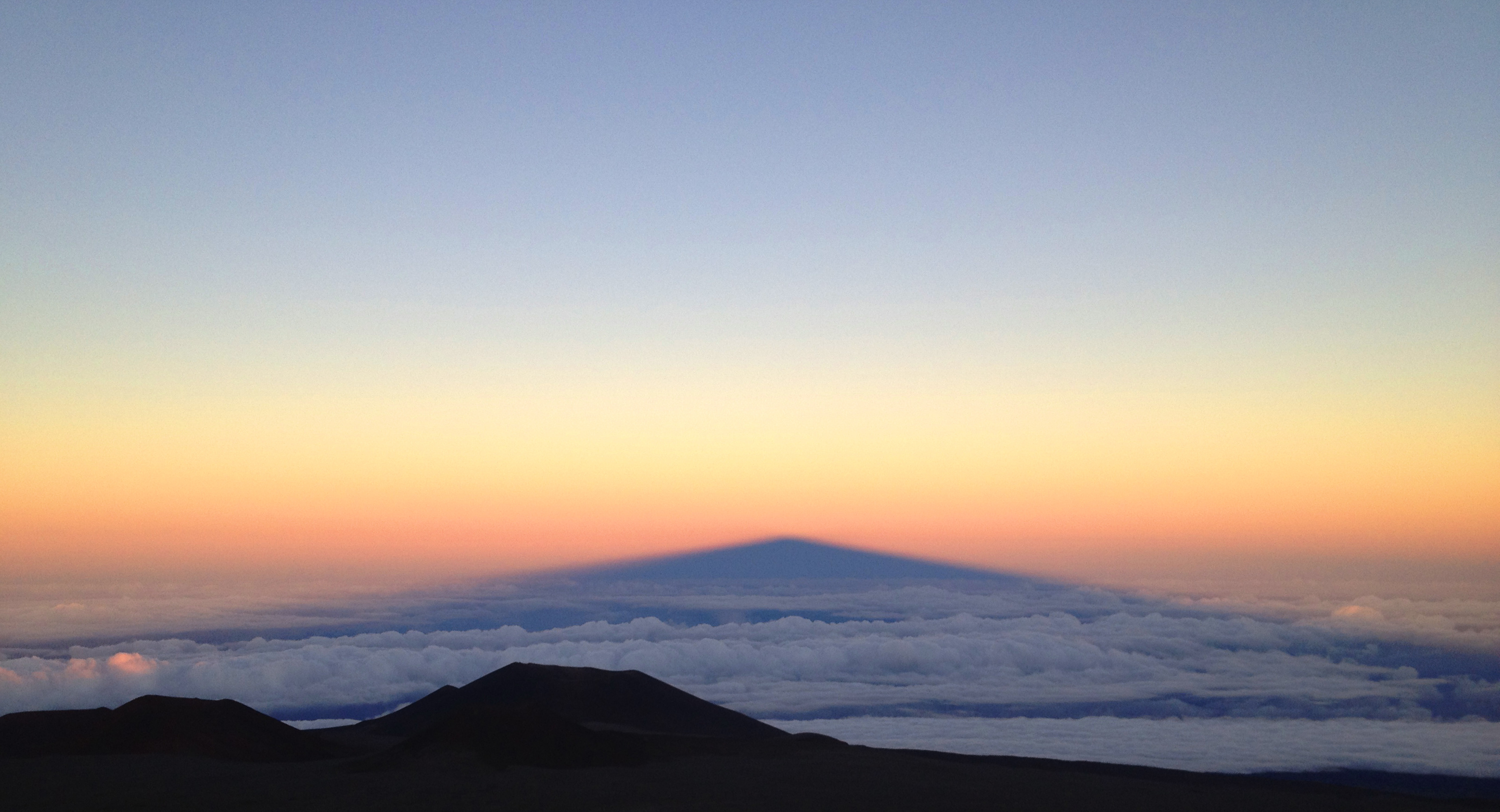 The shadow of Mauna Kea peak on the clouds down below
